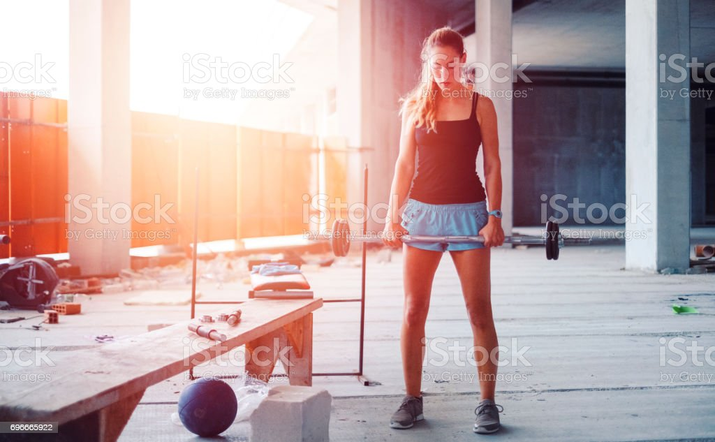 Ghetto gym with woman weightlifting stock photo