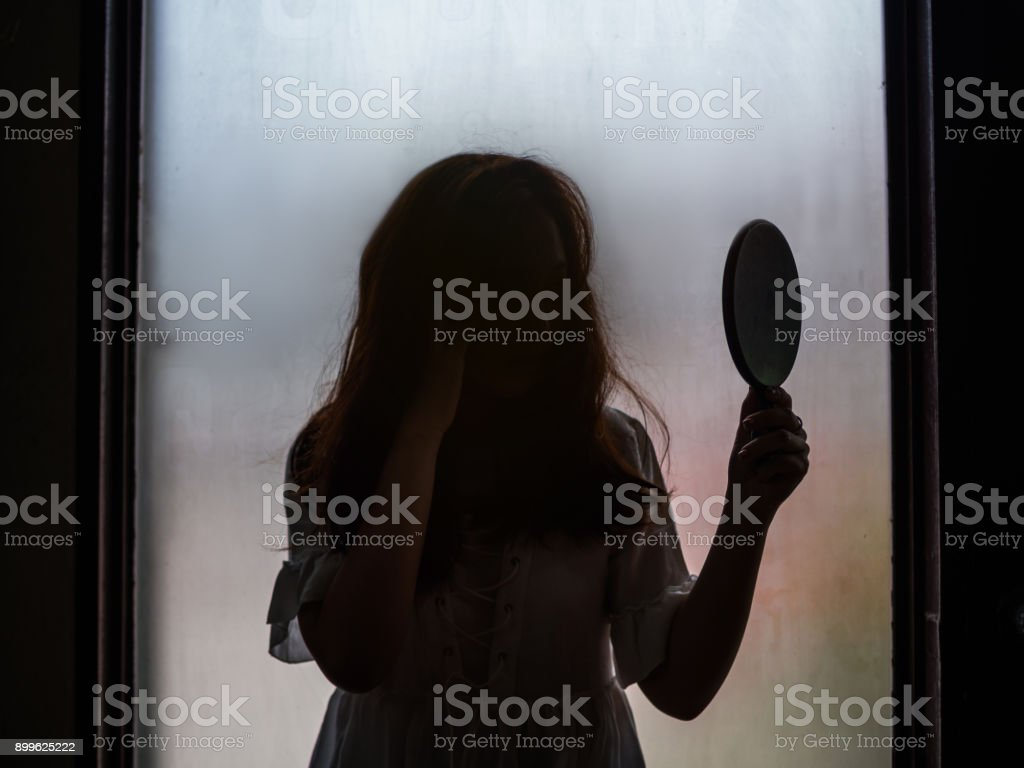 Ghost girl holding mirror standing in front of window stock photo