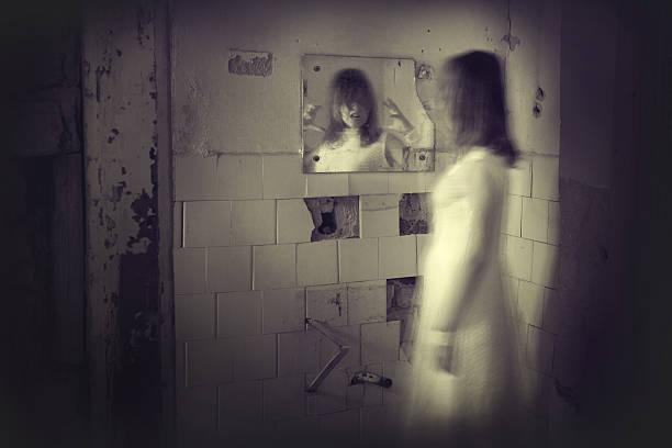ghost mädchen im weißen kleid wird in den spiegel - brüllender tod stock-fotos und bilder