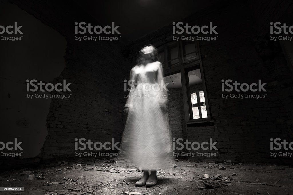 Ghost girl in white dress in ruined house stock photo