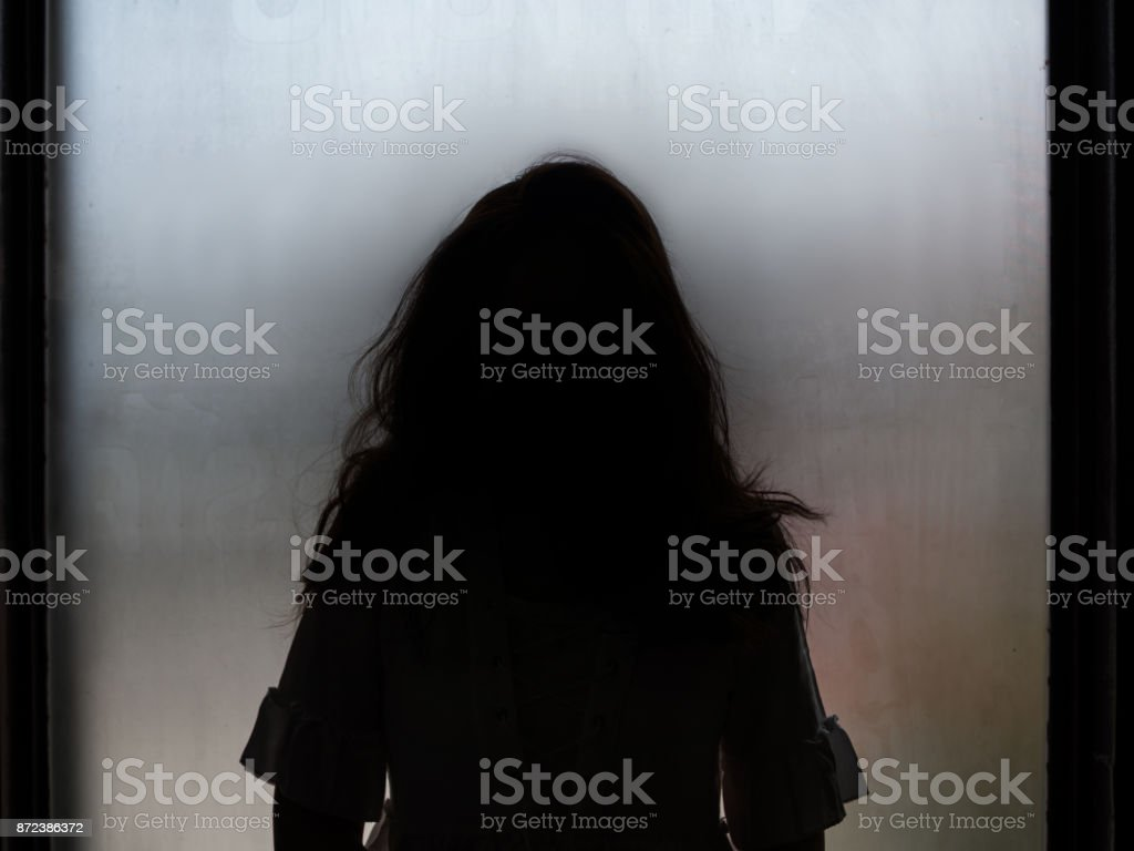 Ghost girl silhouette standing in front of window stock photo