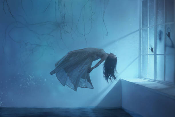 A ghost girl with long hair in a vintage dress. Room under water. A photograph of levitation resembling a dream. A dark Gothic interior with branches and a huge window of flooded light. Art photo stock photo