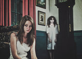 A bizarre scene in a historic mansion of a teenage girl in the foreground with a ghostly young girl crying blood in the corner.