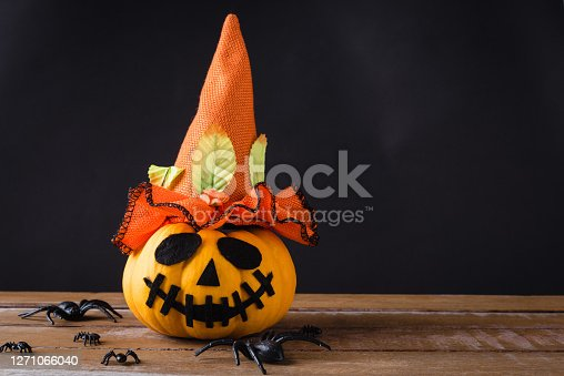 Funny Halloween day party concept ghost pumpkins head jack lantern scary smile wear hat and spider on wooden table and black background, studio shot isolated, Holiday decoration