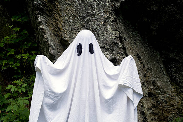 Ghost standing in front of a rock stock photo