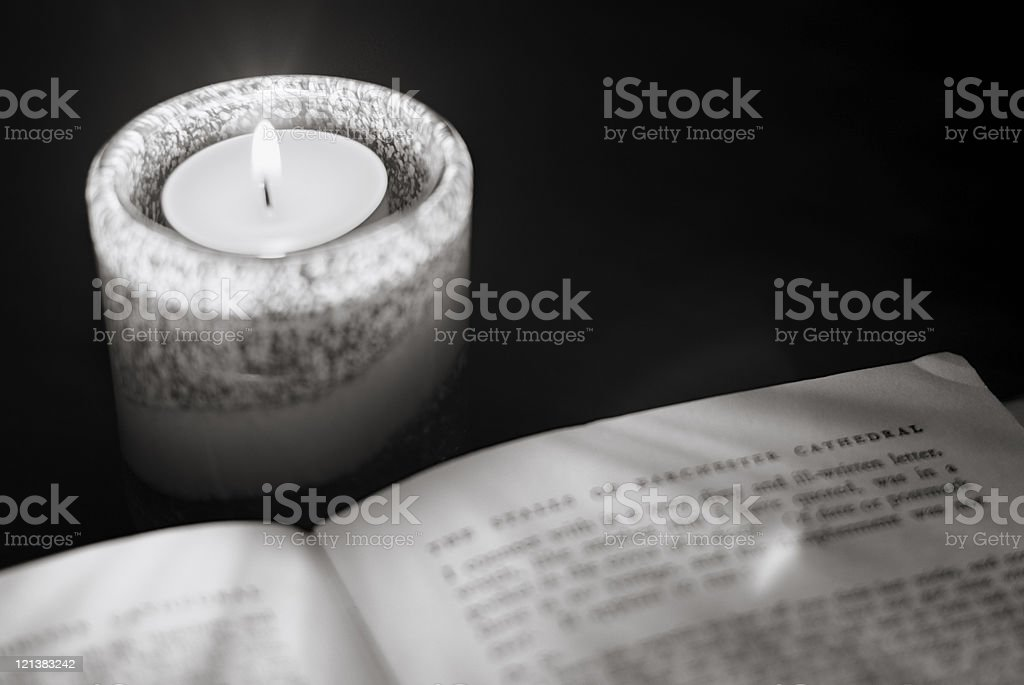 Ghost stories - reading a book at candlelight royalty-free stock photo