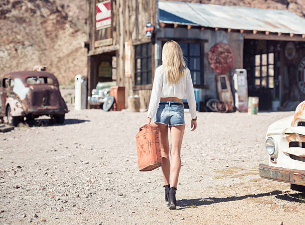 Ghost Town, Woman at a Gas Station Beautiful model with a stunning body and natural long blond hair getting Gasoline at an abandoned Gasstation in Ghost Town sexy girl in blue jeans stock pictures, royalty-free photos & images