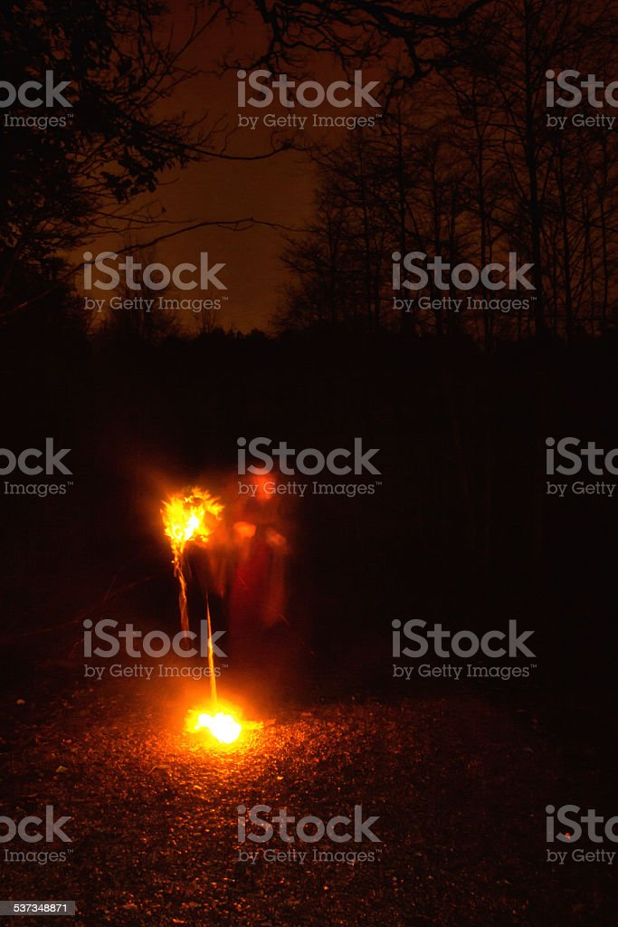 Ghostly female figure in landscape at night stock photo