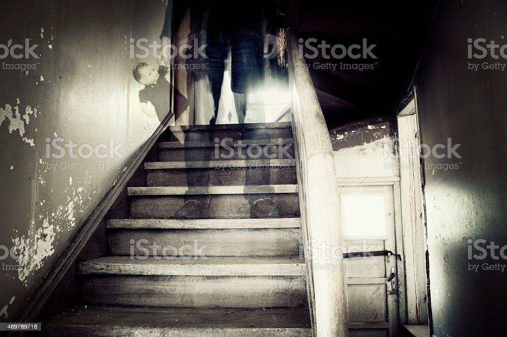 Ghostly figure in a hounted house Ghostly figure standing on stairs inside a hounted house holding doll 2015 Stock Photo