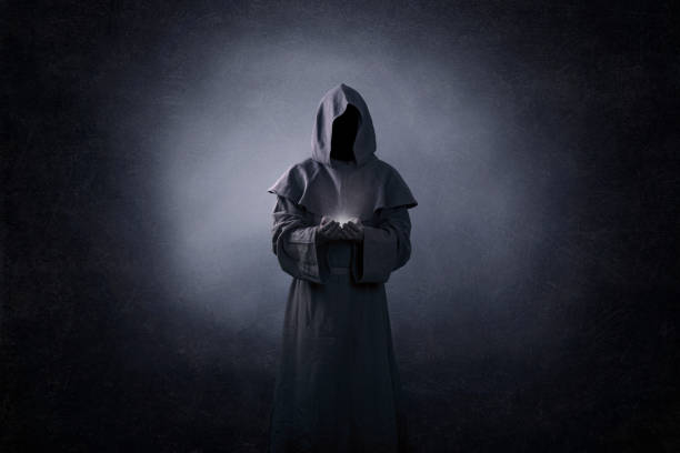 Ghostly figure with light in hands in the dark stock photo