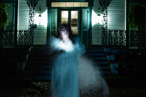 Blurred motion of a woman in long white gown in front of Myrtles Plantation at night, St. Francisville; Louisiana; USA;