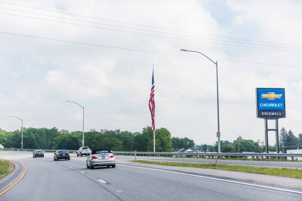 Giant American Flag On Road By Chevrolet Dealership And Cars