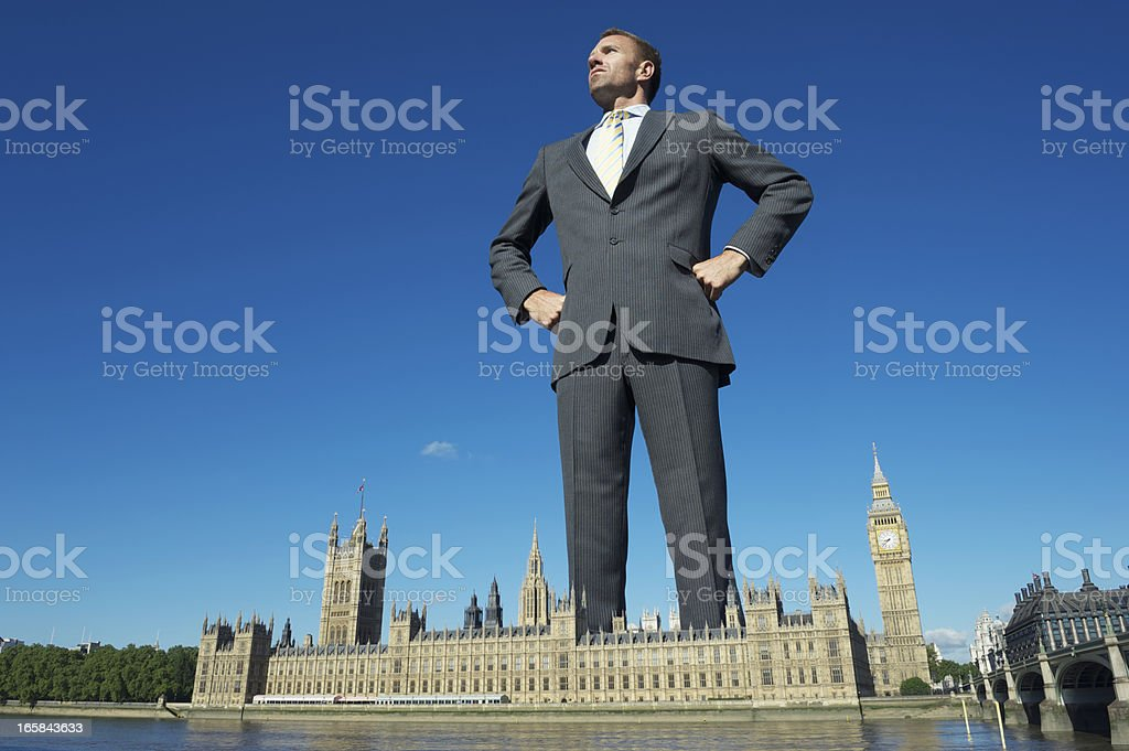 Giant Businessman Towers Over Westminster Palace London stock photo