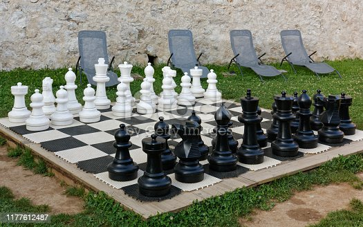 Giant chess in a garden with a stone wall and a few loungers in the background