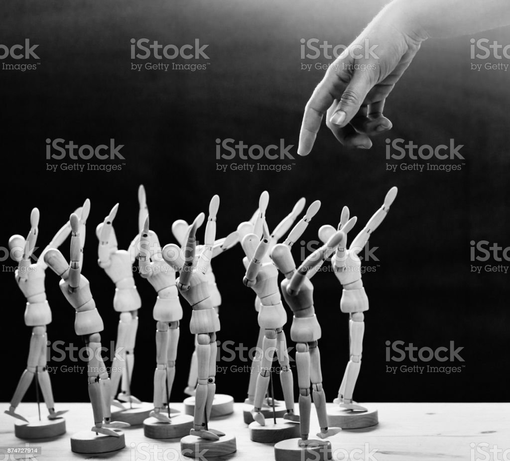Giant human finger approaches crowd of awestruck wooden manikins stock photo