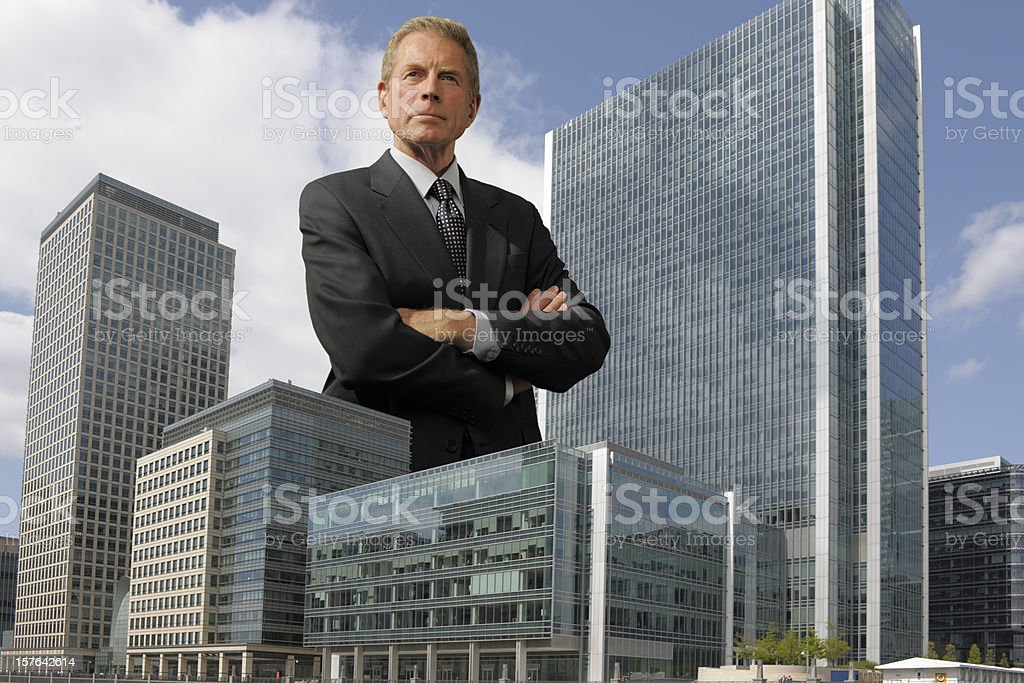 giant man in a suit stands beside two skyscrapers stock photo
