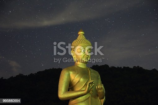 909806032istockphoto giant preaching Buddha statue. standing Buddha sculpture placed under the stars. Thai art Buddhist in Nakornayok's mountain north of Bangkok Thailand. 995880554
