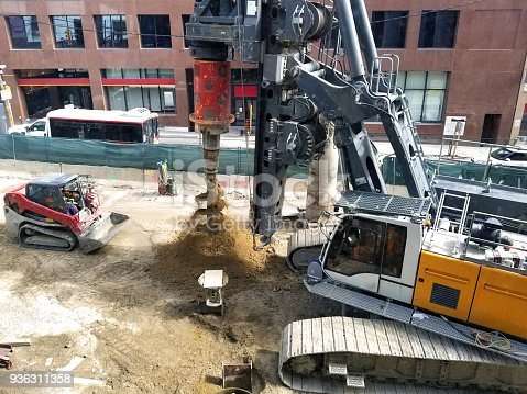 Giant rotary drilling machine that is being operated on a street construction site