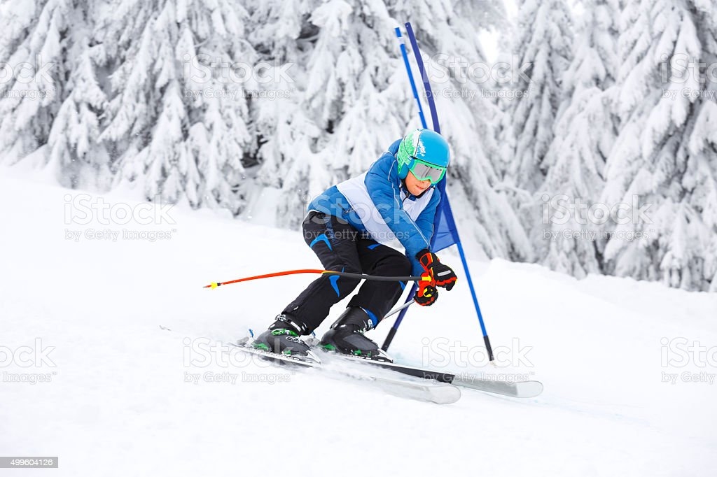 Giant slalom race. A young boy teenager skier, snow skiing carving at...
