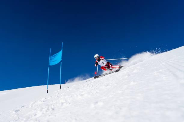 riesenslalom-skirennen ein männlicher skifahrer an blauer tür - skirennen stock-fotos und bilder