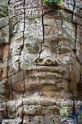 The giant stone relief face at the Buddhist historic site of Angkor Wat in Cambodia, an international landmark.