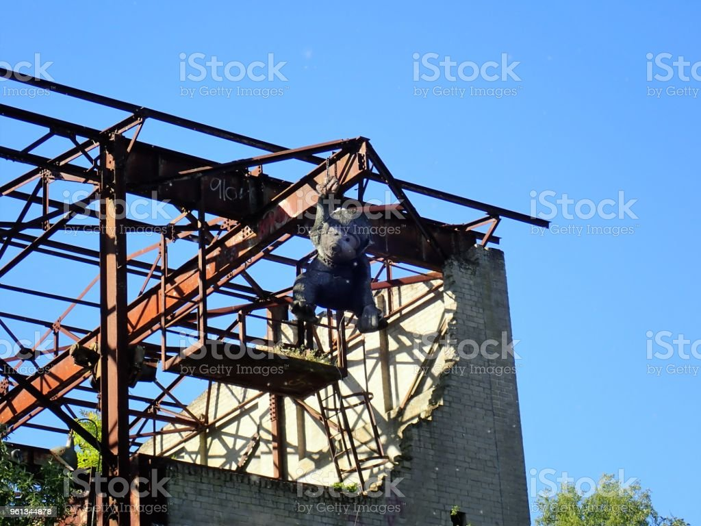 Giant stuffed monkey hanging from abandoned lime works stock photo