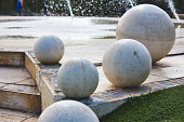 Giant white marble spheres on a modern design fountain in a public park
