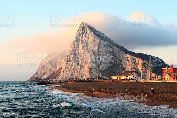 Photo of Gibraltar at sunrise with clouds on top