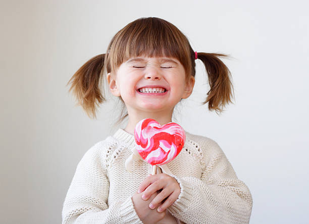 Giddy young girl with a heart-shaped lollipop stock photo