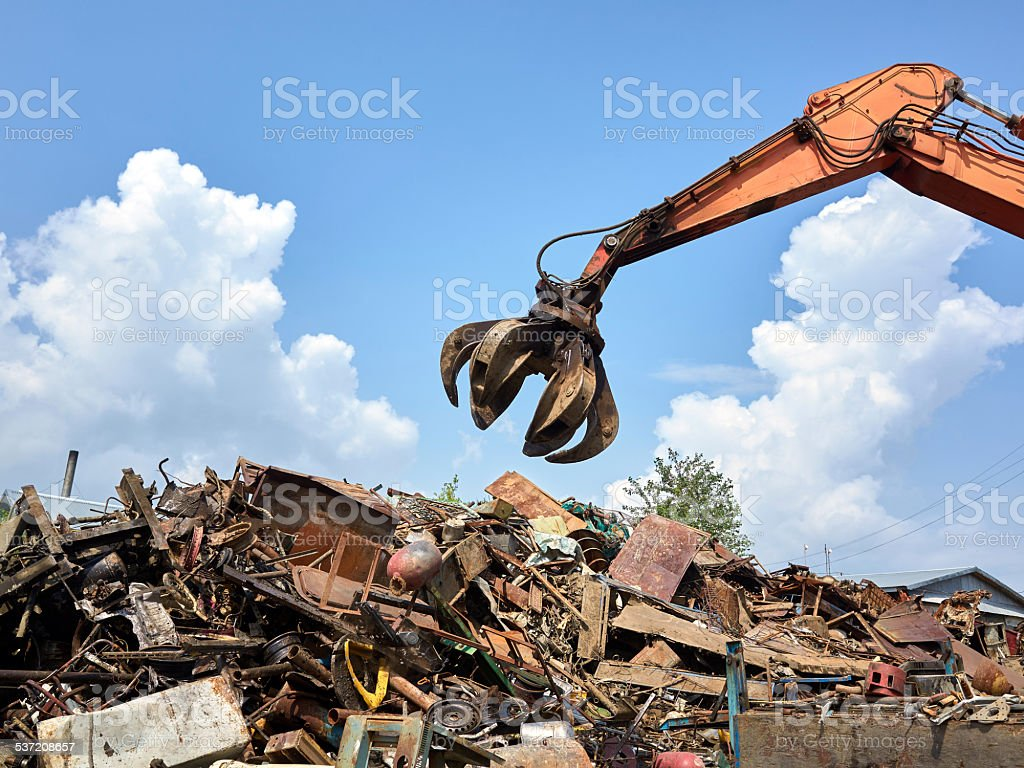 Gidraulic mechanical grabber moves scrap rusty metal heap stock photo