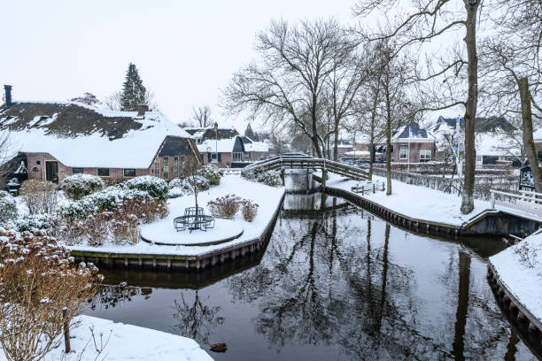Giethoorn village with the canals with snow during a cold but beautiful calm winter day stock photo
