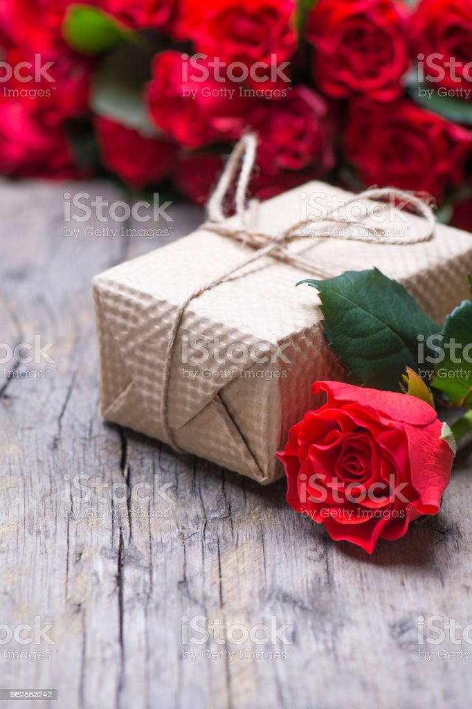 A gift, a bouquet of red roses on a rustic old vintage background - Royalty-free Alcohol Stock Photo
