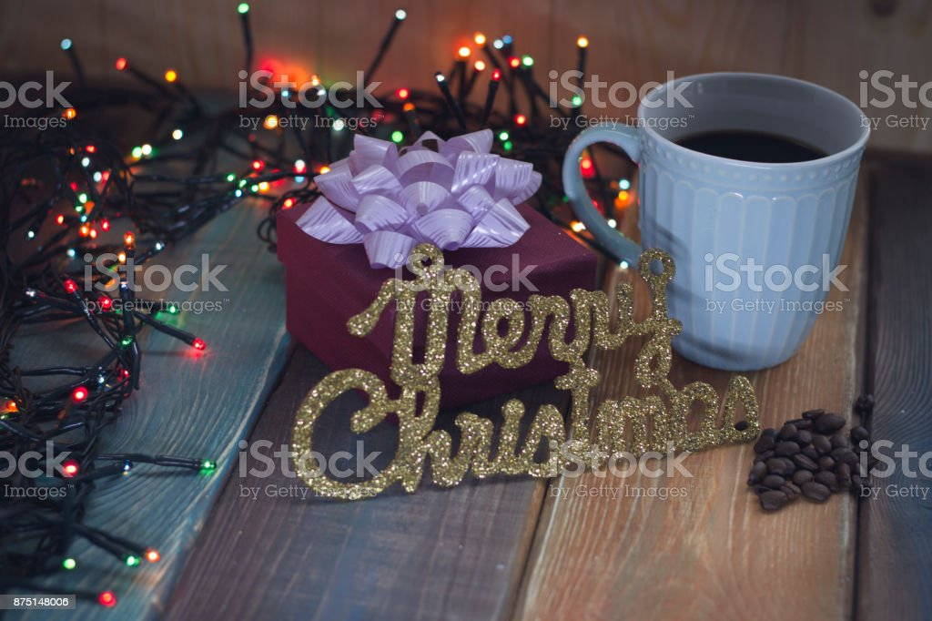 A gift, a gold inscription and a cup of coffee on the table'r'n stock photo