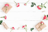 Gift and rose flowers on wooden white background. Flat lay
