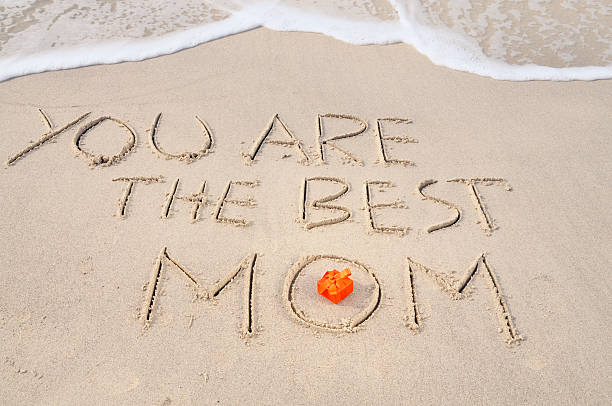 Gift and Words Written in Sand W Wave, Mothers Day stock photo