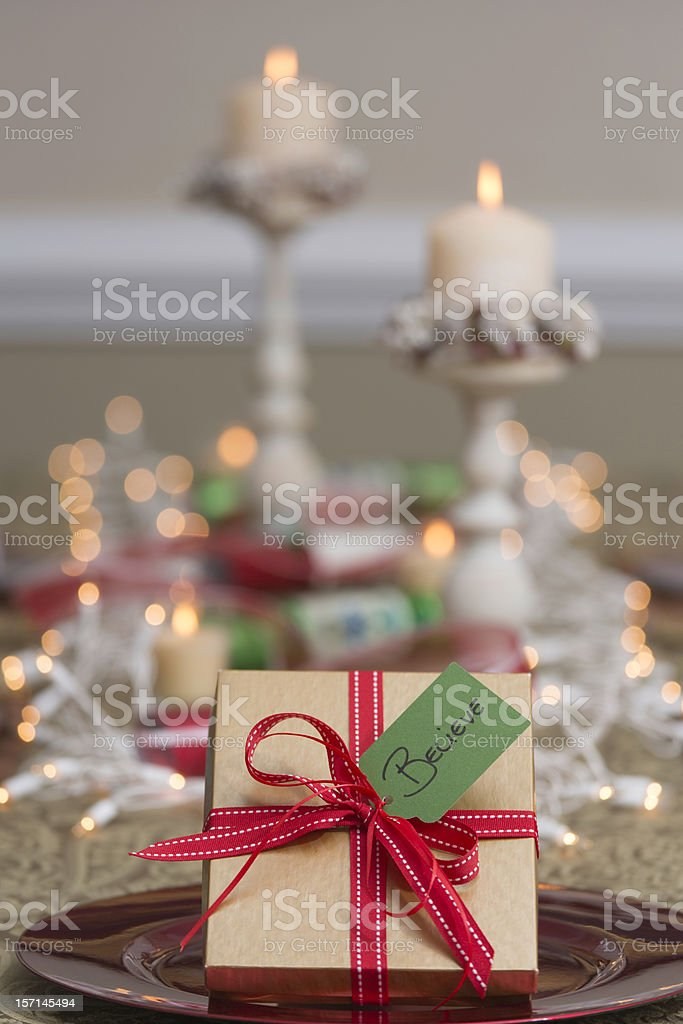 """Gift at festive holiday table with """"BELIEVE"""" tag royalty-free stock photo"""
