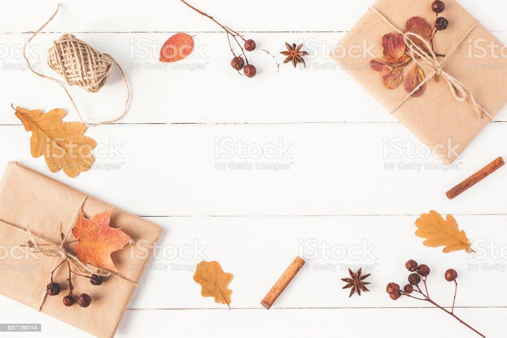 Gift, autumn leaves, cinnamon sticks. Flat lay, top view stock photo