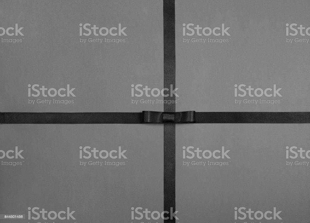 Gift background. Black ribbon on gray paper stock photo