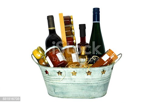 Gift basket full of presents for several occasions. You can see some wine bottles, jam, mustard, vinegar as well as some balsamic vinegar.