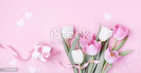 659293084 istock photo Gift box and beautiful spring tulip flowers on pastel pink background. Banner for Women Day, Mother day. Flat lay. 1130305861