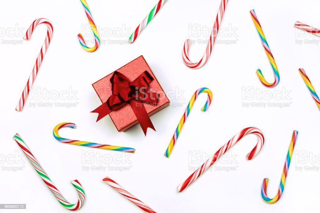 Gift box and candy canes. Concept of Christmas time. Flat lay stock photo