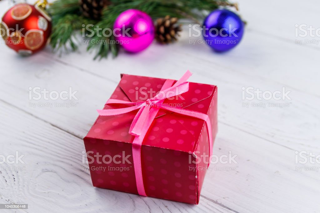 Gift box and Christmas decorations on white wooden table