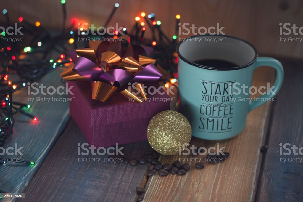 Gift box and cup of coffee, gold inscription on the table stock photo
