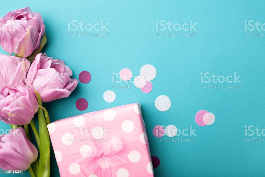 Gift box wrapped in polka dot paper and pink tulip flowers on blue...