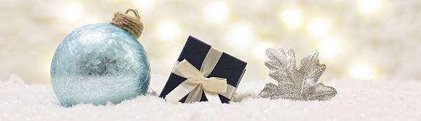 gift box and glass ball are in the snow. - weihnachtsspende stock-fotos und bilder