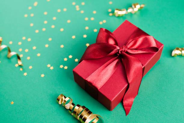 Geschenkbox und goldene Dekorationen und Funken auf hellgrünem Hintergrund – Foto
