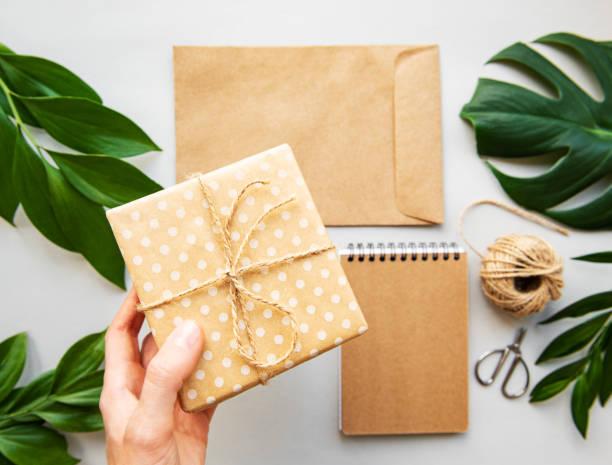 geschenkbox, umschlag und notizbuch mit grünen blättern - eco bastelarbeiten stock-fotos und bilder