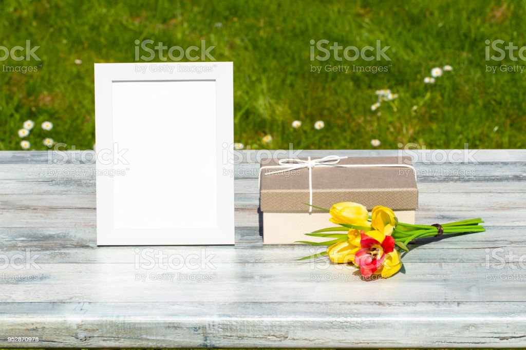 Gift box, flowers and white vintage frame with place for your text on...