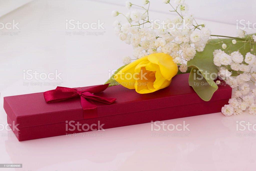 Gift box, flowers of yellow tulips and graceful gypsophila . The...