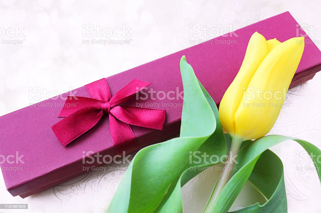 Gift box, flowers of yellow tulips. The concept of a gift to a woman....